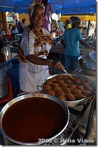 ...e posa em frente aos suculentos acarajés